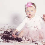 Baby smashing birthday cake