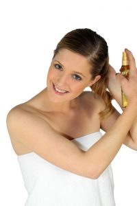 Woman spraying her hair with a product
