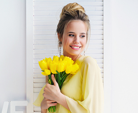 woman with topknot holding yellow tulips