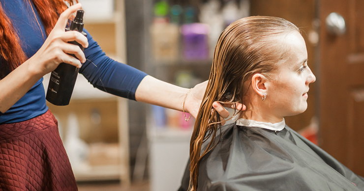 hair stylist spraying womans hair