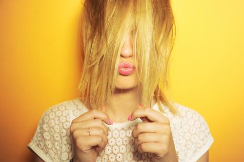 closeup portrait blond woman pulling hairs