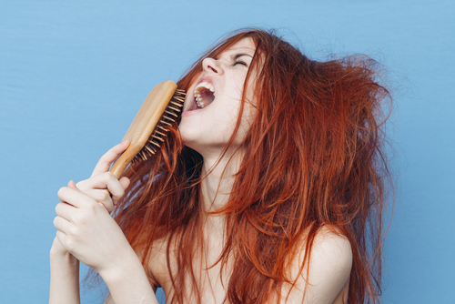 woman shouting combing hair tangles