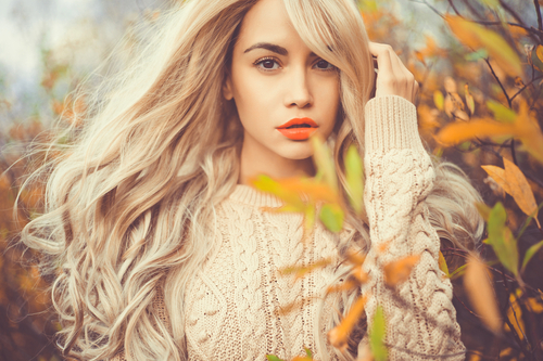 young lady surrounded by autumn leaves